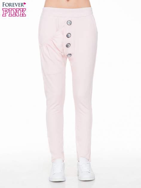 Różowe dresowe spodnie baggy z guzikami i ozdobnymi kieszonkami                                  zdj.                                  1