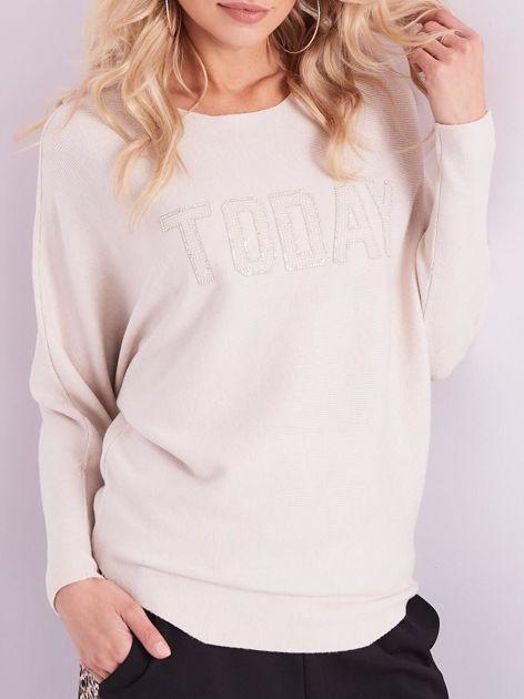 Beżowy sweter oversize z błyszczącym napisem                              zdj.                              2