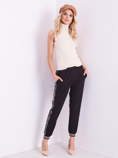 Czarne spodnie z wężowym lampasem                              zdj.                              7