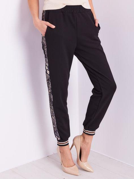 Czarne spodnie z wężowym lampasem                              zdj.                              4