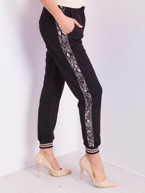 Czarne spodnie z wężowym lampasem                              zdj.                              6