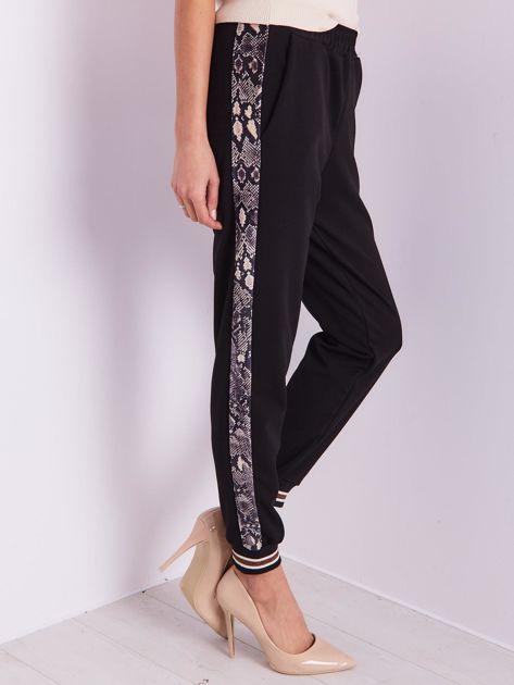 Czarne spodnie z wężowym lampasem                              zdj.                              2