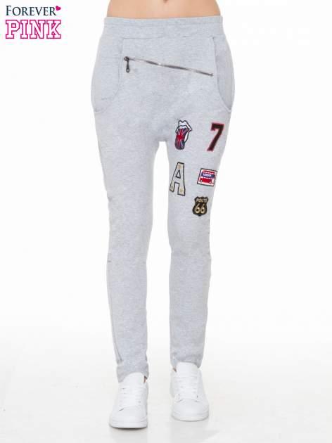 Szare spodnie dresowe typu baggy z naszywkami                                  zdj.                                  1