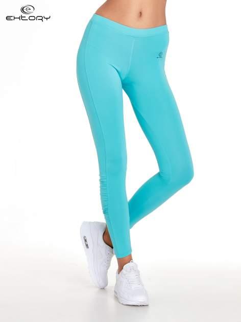Turkusowe legginsy sportowe termalne z drapowaniem