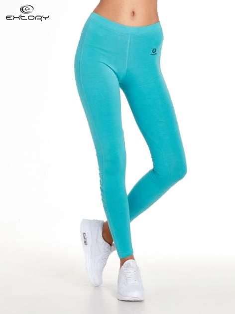 Turkusowe legginsy sportowe z drapowaniem