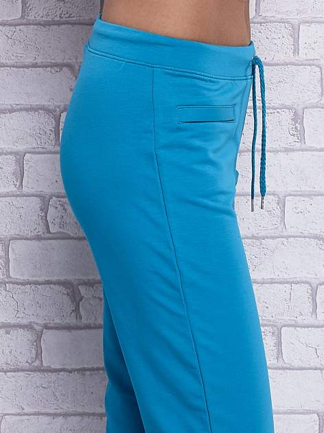Turkusowe spodnie dresowe capri z wszytymi kieszonkami                                  zdj.                                  5