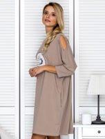 Beżowa sukienka damska oversize z perełkami i okrągłą naszywką                                  zdj.                                  5