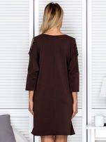 Brązowa sukienka damska oversize z perełkami i okrągłą naszywką                                  zdj.                                  2