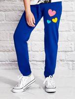 Ciemnoniebieskie spodnie dresowe dla dziewczynki z nadrukiem serc                                  zdj.                                  1