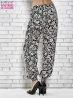 Czarne zwiewne spodnie alladynki we wzór kwiatków                                  zdj.                                  2