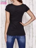 Czarny t-shirt z falbanami i złotą kokardką