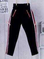 Granatowe spodnie dresowe dla dziewczynki z taśmą tricolor                                  zdj.                                  1