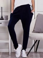 Granatowe spodnie dresowe ze ściągaczami przy kieszeniach                                  zdj.                                  1