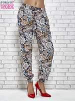 Granatowe zwiewne spodnie alladynki we wzór kwiatowy                                  zdj.                                  1