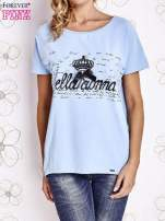 Jasnoniebieski t-shirt z ozdobnym napisem i kokardą                                  zdj.                                  1