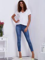 Jasnoniebieskie jeansy damskie o kroju slim z drobnymi przetarciami                                  zdj.                                  4