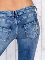 Niebieskie jeansowe spodnie rurki z przetarciami i haftami