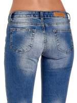 Niebieskie spodnie jeansowe skinny 7/8 z dziuarmi na kolanach