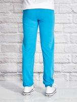 Turkusowe spodnie dresowe dla dziewczynki z napisem FOLLOW MY FEET                                  zdj.                                  2